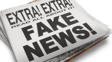 """The front page of a newspaper with the headline """"Fake News"""" which illustrates the current phenomena. Front section of newspaper is on top of loosely stacked remainder of newspaper. All visible text is authored by the photographer. Photographed in a studio setting on a white background with a slight wide angle lens."""
